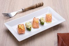 Flambe salmon and avocado with lemon sauce. On white plate Royalty Free Stock Photo