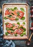 Flambee de Tarte avec des saumons, épinards et tomates, faisant cuire la préparation sur le fond rustique de table de cuisine photos stock