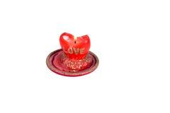 Flambez les bougies rouges sous forme de coeur avec l'amour de mot dessus Photographie stock libre de droits