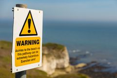 Flamborough Head, East Riding of Yorkshire, UK. Warning sign with blurry Flamborough Head coast and cliffs in the background, near Bridlington, East Riding of royalty free stock image