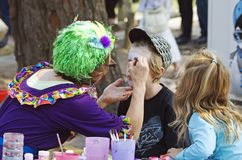 Flamboyant colorful woman painting faces of children at carnival. A very flamboyant woman wearing a sparkly lime bright green wig and colorful clothing is stock photography