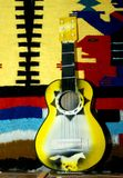 Flamboyant Guitar. Bright yellow guitar sits on a shelf at a souvenir shop.  Brightly colored blanket hangs behind guitar Stock Image