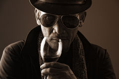 Flamboyant hustler with sinister eye. Old flamboyant hustler with sinister eye behind glasses Royalty Free Stock Image