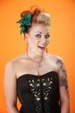 Flamboyant Lady. Middle aged, flamboyant lady with a confident smile on orange background Stock Photos