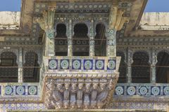 Flamboyant Projecting Balcony, City Palace, Udaipur, India. Carved, painted and tiled in a variety of patterns, styles and colors, this is one of many Mughal stock image