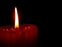 Flame. A red ribbed candle and flame on black background Stock Images