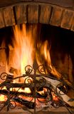 Flame. Close-up of fire in brown brick chimney set on in the evening Royalty Free Stock Photo