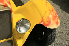Flame. Yellow car front end with headlight with orange and red flames stock image