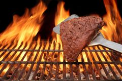 Flame Broiled Steak on the BBQ Grill. Flame Broiled Steak and Spatula on the BBQ Grill. Flames on the black Background stock photography