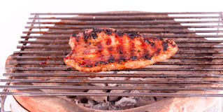 Flame broiled steak on a grill Stock Image
