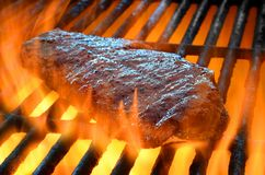 Flame broiled steak on a grill. Steak on a open flame grill royalty free stock photography
