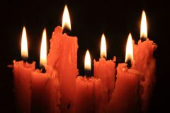 Flame of burning candles. Isolated on black background Stock Photos
