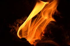 The flame burns. Burning flame bursts out of the hole between the coals Royalty Free Stock Photos