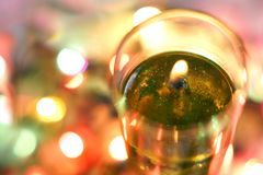 Flame of candle. Garland lights in the background royalty free stock images