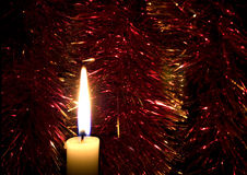 Flame of a candle. Against a bright Christmas tinsel Stock Photo