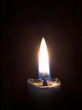 Flame of a candle. Candle burning in darkness, a match and a flame. Objects over black Royalty Free Stock Photography