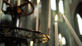 Flame of candle in candelabrum. Old vintage candelabrum in cathedral. Close-up flame of burning candle, one candle light from another defocused interior at stock footage