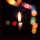 Flame of a candle on a dark background with colored bokeh Stock Image
