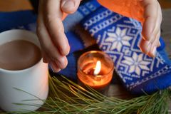 Flame from a candle warms hands Royalty Free Stock Image