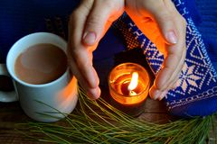 Flame from a candle warms hands. Candle & coffee warms Royalty Free Stock Images