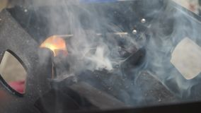 Flame from charcoal in bbq. A medium shot of coals, being prepared for barbecue. Starting to heat up the coals until they glow. Sm. Oked going out of the stock footage