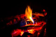 Flame on embers in dark Royalty Free Stock Image