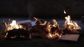Flame of fire burns pile of documents associated with war and destruction