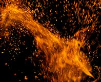 Flame of fire with sparks on a black background royalty free stock photo