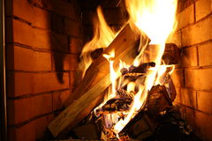 Flame in a fireplace. Flaring tongues of flame on coals in a fireplace Royalty Free Stock Image