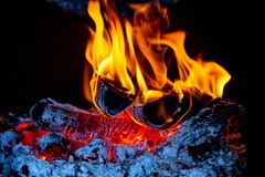 Flame in fireplace. Burning wood. Flame in fireplace. Burning piece of wood. Fire and warm at home Stock Photography