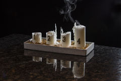 The flame from fourth candle has extinct, only smoke remains. Fourth advent fades away Stock Photos