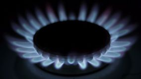 Flame of a gas burner in the kitchen stove is gradually fading Stock Photos