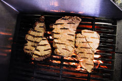 Flame grilled meat on a grill Royalty Free Stock Image