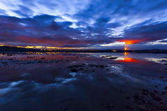 Flame on horizon of night cloudscape scene over water surface Royalty Free Stock Image
