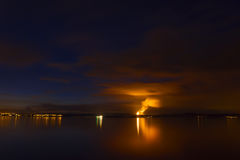 Flame on horizon of night cloudscape scene Royalty Free Stock Image