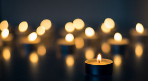 Flame of many candles burning on the background blue color Royalty Free Stock Photo