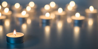 Flame of many candles burning on the background blue color Stock Photos