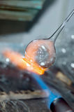 A flame and melting glass piece Royalty Free Stock Photography