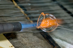 A flame and melting glass piece Stock Photos