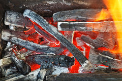 Flame over hot wood-burning coals Royalty Free Stock Photo