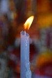 Flame of white melting candle in temple or church Royalty Free Stock Images