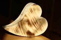 Flamed wood heart on table with dark background Royalty Free Stock Images