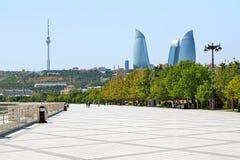Flamee los rascacielos de las torres, la torre de la TV y el terraplén del mar Caspio Fotografía de archivo libre de regalías