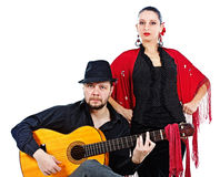 Flamenco couple. Portrait of a women flamenco dancer in black and red clothes, standing behind a men guitarist wearing black hat, playing his guitar, both Royalty Free Stock Photos
