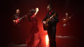 Flamenco dance performed by a professional girl next to playing guitarists music. Light from behind. smoke background stock video footage