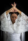 Flamenco dancer backs with white dress and hands crossed up. On black background stock photography