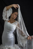 Flamenco dancer backs with white dress and hands crossed up. On black background royalty free stock image