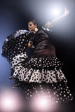 Flamenco dancer in motion. Young gorgeous woman in brown color silk dress with polka dots performing flamenco dance in the spotlight Stock Photography