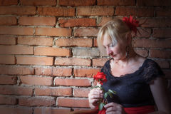 Flamenco dancer with red rose in her hand. Middle aged woman dressed in costume of Flamenco dancer is holding a red rose in her hand. Old brick wall is in the Royalty Free Stock Photography