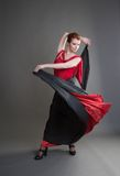 Flamenco. Dancer swinging skirt on a grey background Stock Photography